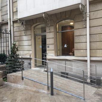 Garde corps ou rampe sur mesure en inox brossé pour rampe d'accès à un immeuble parisien avec porte et fenêtre en inox