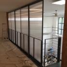Grandes portes coulissantes sur mesure posées sur mezzanine avec accès à l'escalier