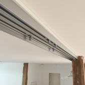 Vue des rails de guidage des panneaux coulissants avant habillage par de la tôle aluminium blanche pliée