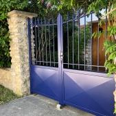 Portail en acier bleu avec barreaux ronds et volutes en fer forgées et pointes de diamant